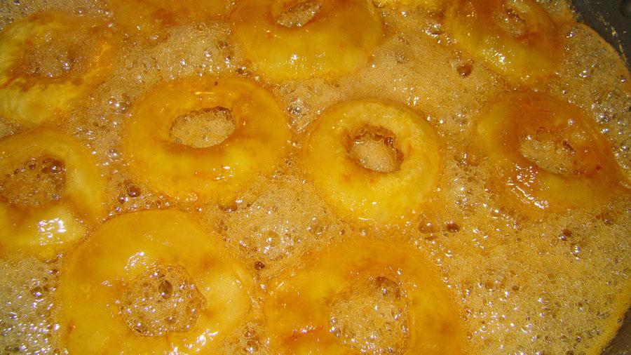 geschälte Zitrusfrüchte kochen in Zucker und Honig